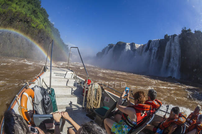 Tourists take boat to base of falls — Stock Photo