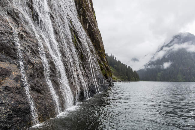 Води, що збігають вниз скелі в туманний фіорд Національний парк — стокове фото