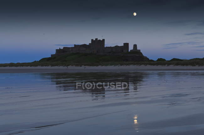 Bamburgh Castle under a full moon — Stock Photo