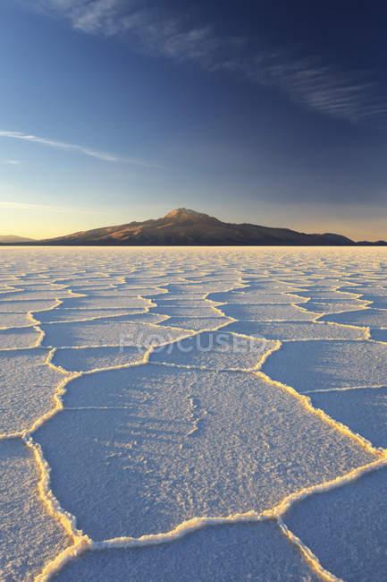Volcán Andino se eleva sobre el Salar de Uyuni - foto de stock