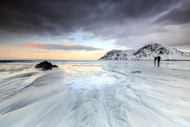 Puesta de sol y excursionistas en Skagsanden playa - foto de stock
