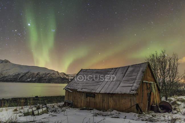 Aurora Boreal ilumina la cabina madera - foto de stock