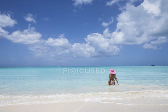 Woman in pink hat in turquoise waters — Stock Photo