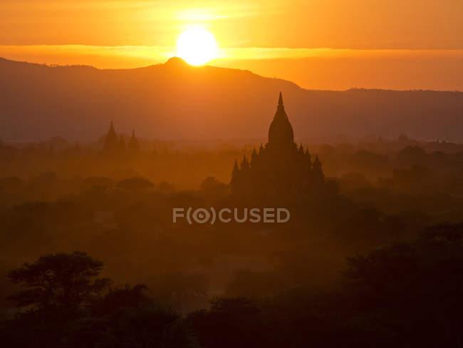 Pôr do sol sobre templos budistas — Fotografia de Stock