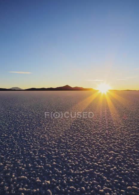 Puesta de sol sobre el Salar de Uyuni - foto de stock