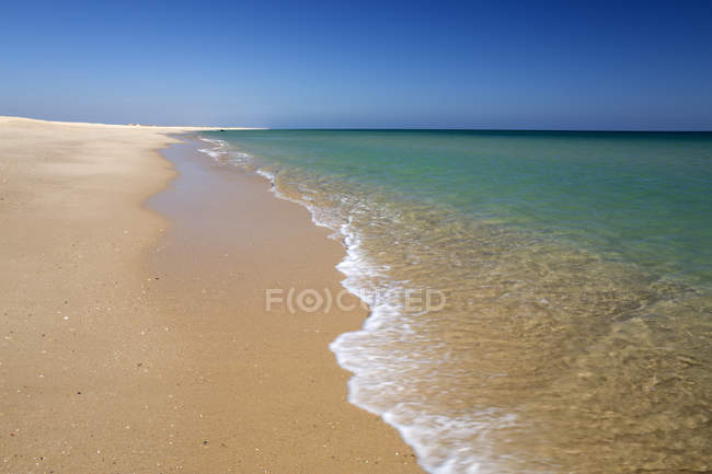 Empty white sand beach and breaking waves — Stock Photo