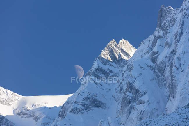 Blue sky and moon on snowy ridges — Stock Photo