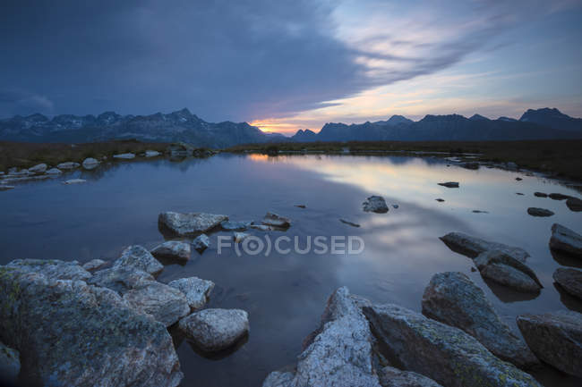 Lights of sunrise reflected in alpine lake — Stock Photo