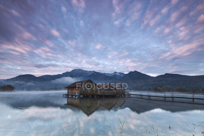 Pink clouds at sunset and wooden huts — Stock Photo