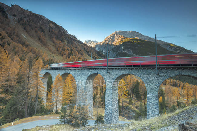 Red train on viaduct — Stock Photo