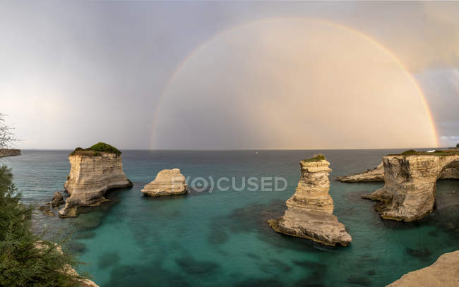 Rainbow frames rocky cliffs — Stock Photo