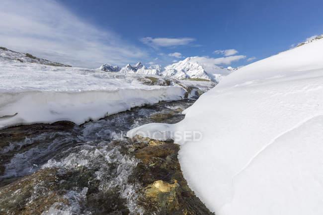 Creek im verschneiten Vallley mit Monte Disgrazia — Stockfoto
