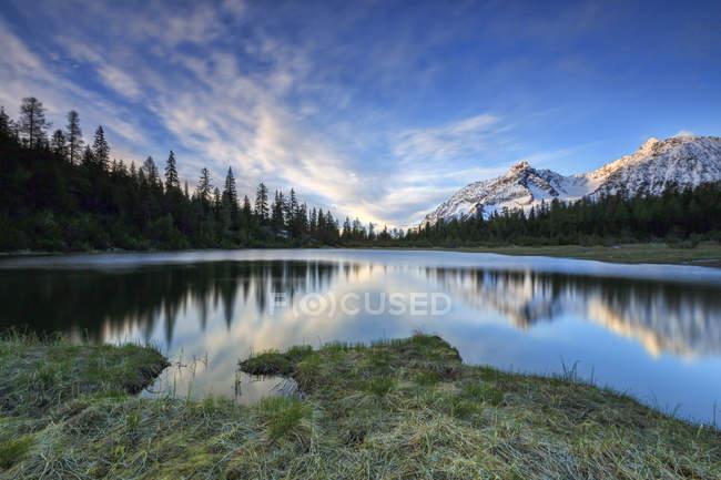 Sunrise frames snowy peaks reflected in Lake Entova — Stock Photo