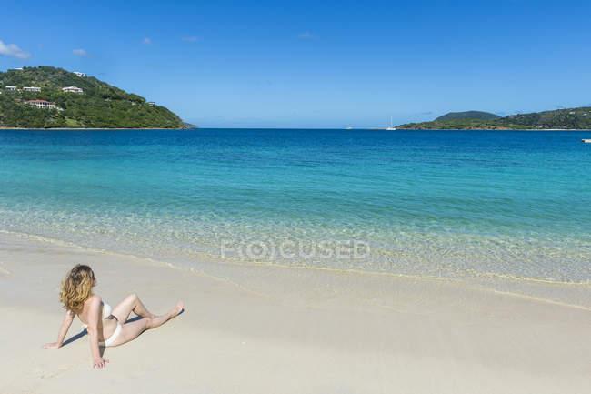 Жінка розслабляючий на довгому пляжі затоки — стокове фото