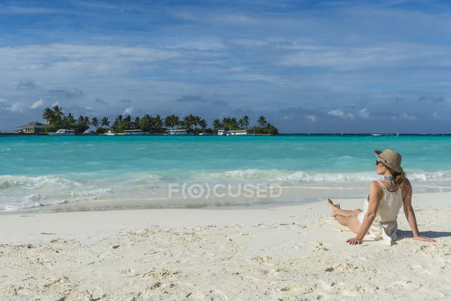 Woman sitting on white sand beach — Stock Photo