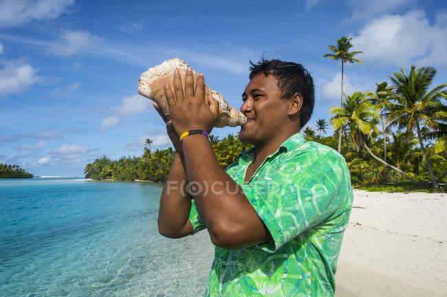 Uomo locale che soffia un'enorme conchiglia — Foto stock
