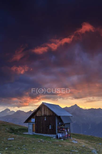 Capanna di legno sotto cielo infuocato — Foto stock