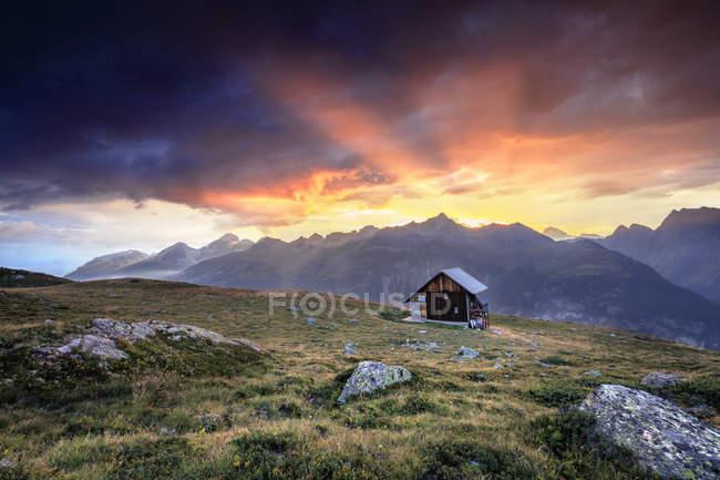 Cabane en bois sous le ciel de feu — Photo de stock