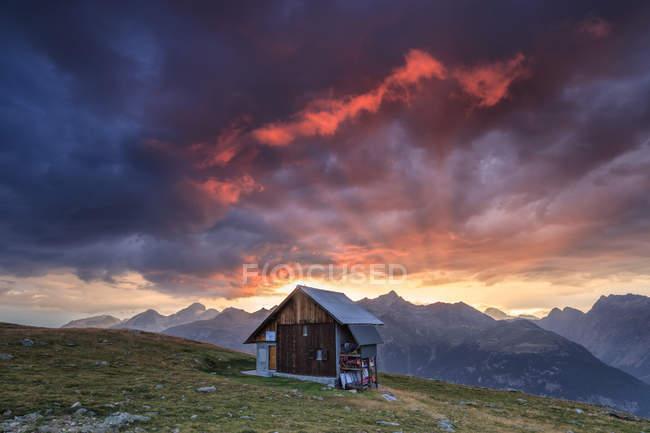 Cabane en bois encadré par fiery sky — Photo de stock