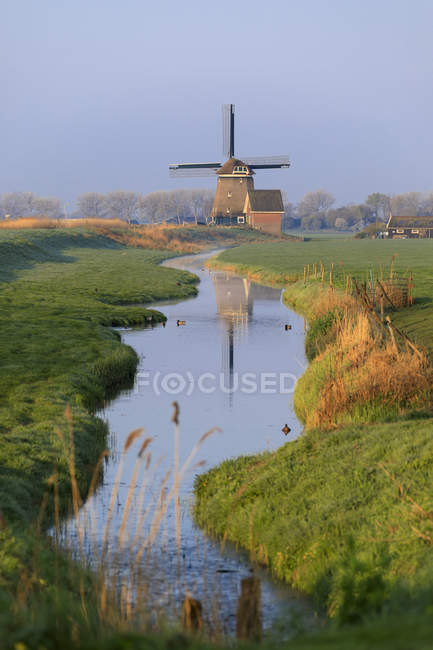 Typical windmill reflected in the canal — Stock Photo
