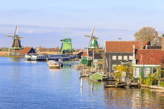 Wood houses and windmill reflected in River — Stock Photo