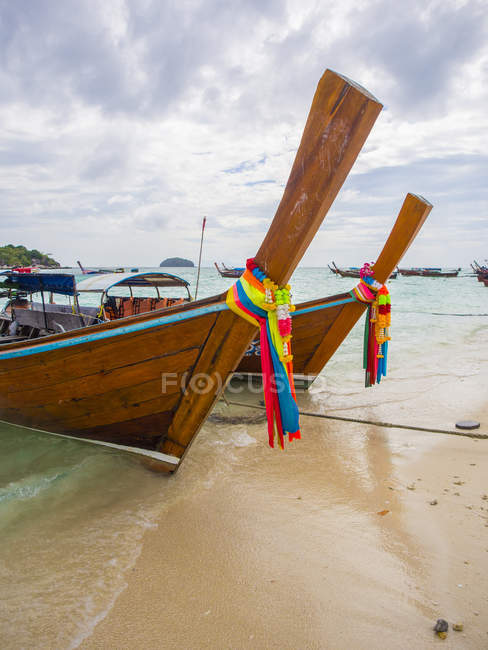 Long-tail boats with coloured-ribbon offerings — Stock Photo