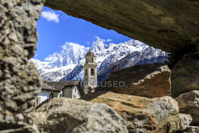 Bell tower and snowy peaks — Stock Photo