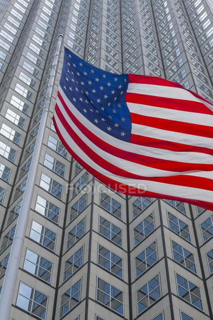 Drapeau américain contre des gratte-ciel — Photo de stock