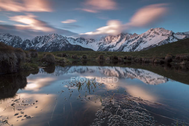 Pink clouds reflected in water at dawn — Stock Photo