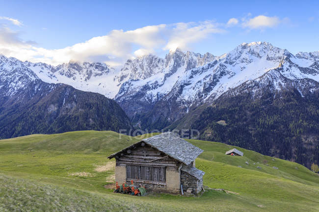 Huts framed by snowy peaks at dawn — Stock Photo