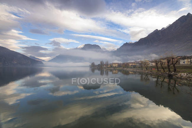 Mountains and village reflected in Lake — Stock Photo