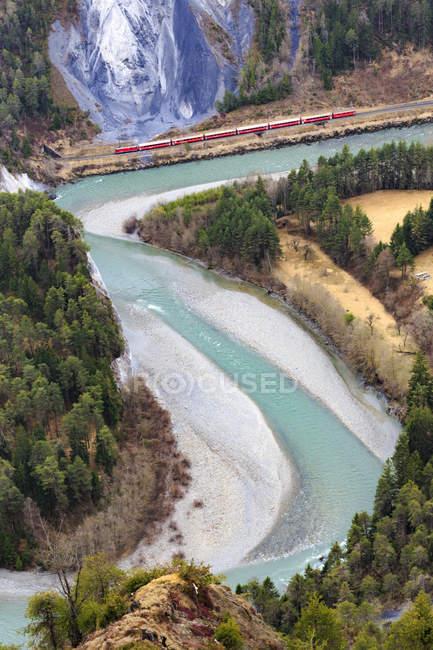 Красный поезд проходит вдоль реки Рейн — стоковое фото
