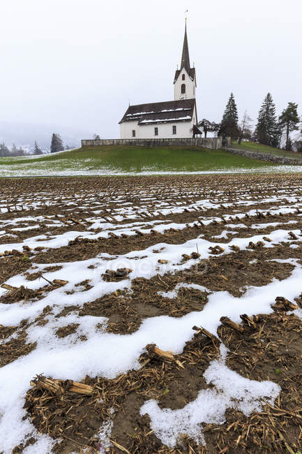 Fields ploughed in front of church — Stock Photo
