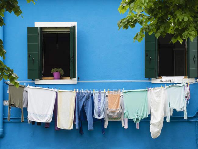 Laver en ligne devant la maison bleu vif — Photo de stock