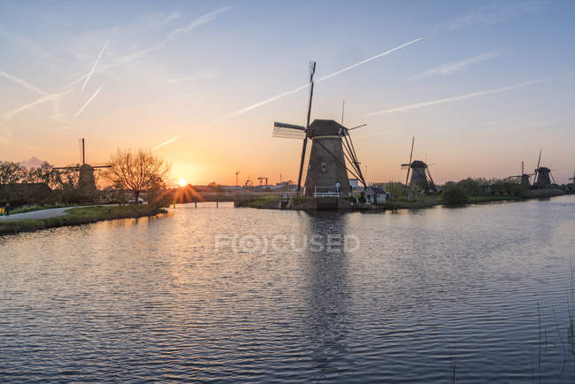 Windmill on canal at sunset — Stock Photo