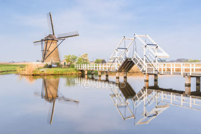 Windmill and sluice on canal — Stock Photo