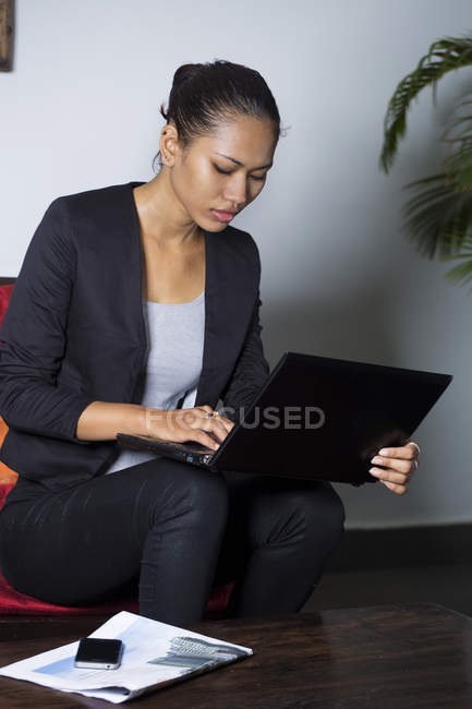 Confident cambodian businesswoman using laptop — Stock Photo