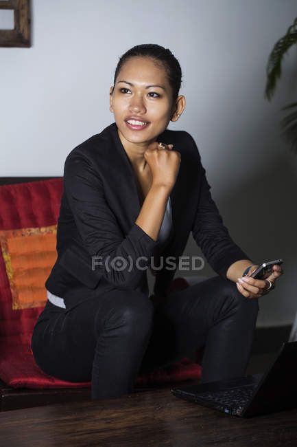 Cambodian businesswoman sitting with smartphone and laptop — Stock Photo