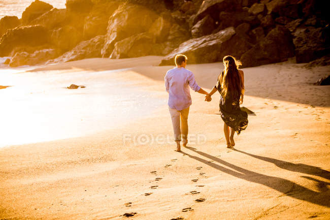 Couple holding hands while walking on beach, Malibu, California — Stock Photo