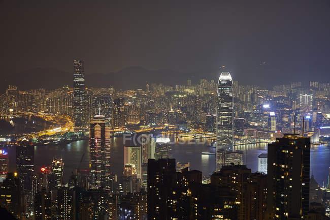 Vista aérea en la noche de Hong Kong y el puerto de Victoria - foto de stock