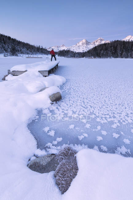 Homme debout sur le rivage du lac gelé — Photo de stock