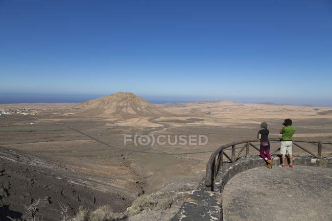 Tourists standing at Mirador de Vallebron and looking towards Tindaya volcano on the island of Fuerteventura, Canary Islands, Spain, Atlantic — стоковое фото