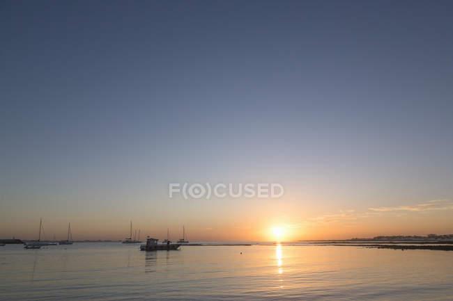 Salida del sol sobre el mar y barcos - foto de stock