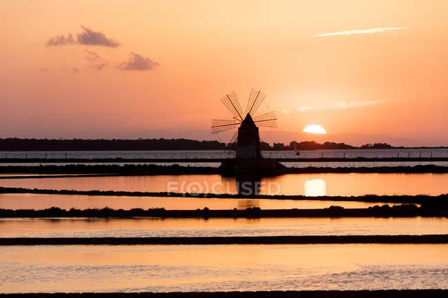 Moinho de vento e pântano de sal ao pôr do sol — Fotografia de Stock