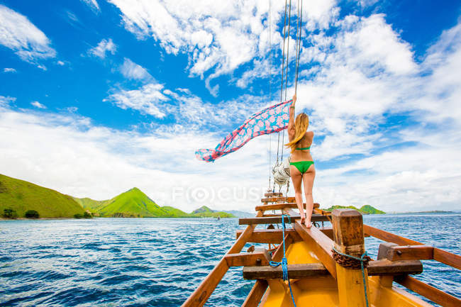 Girl perching on bow of Phinisi Boat, sailing through Komodo National Park, Indonesia, Southeast Asia, Asia — Photo de stock
