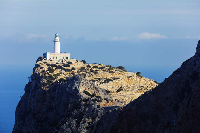 Cap de Formentor lighthouse on cliff under blue sky, Majorca