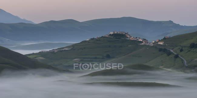 Фортепиано Grande плато и Кастеллучио деревня на рассвете, Умбрия, Италия — стоковое фото