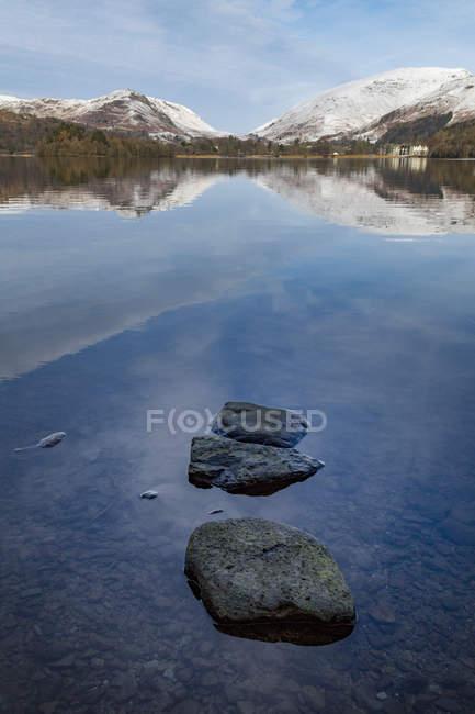 Pietre in acqua poco profonda e neve coperto montagne di sfondo, Parco nazionale di Lake District, Cumbria, Inghilterra, Regno Unito — Foto stock