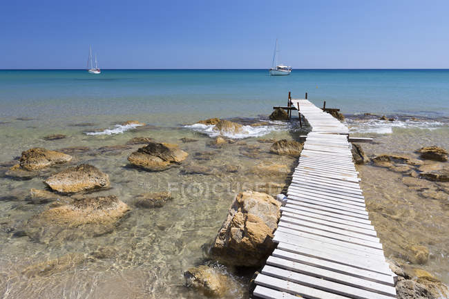 Wooden pier and clear turquoise sea with yachts at Provatas beach, Milos, Cyclades, Aegean Sea, Greek Islands, Greece — Stock Photo