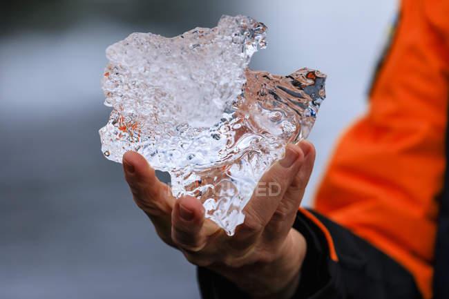 Крупный план человеческой руки, держащей кусок льда ледника — стоковое фото